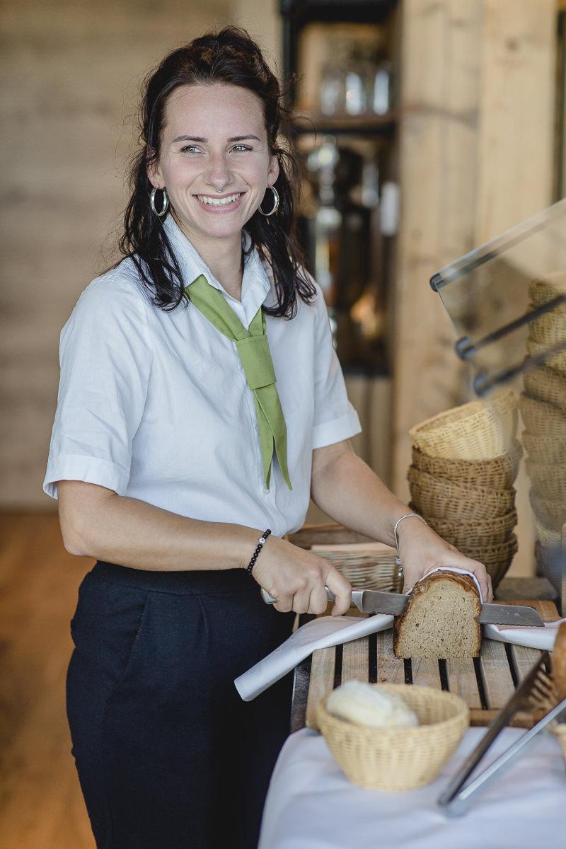 eine Service-Mitarbeiterin schneidet für das Frühstück Brot auf | Foto: Hanna Witte