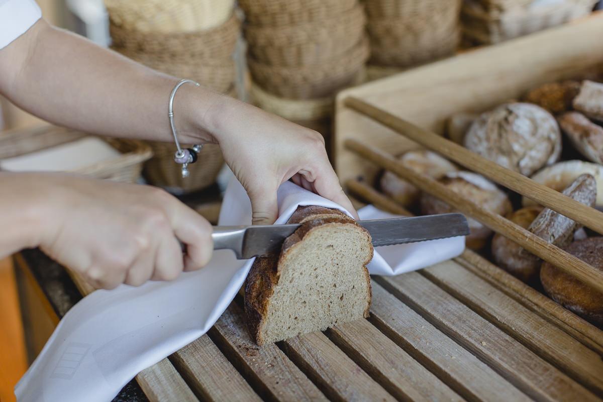 eine Service-Mitarbeiterin im Hotel schneidet für das Frühstück Brot auf | Foto: Hanna Witte