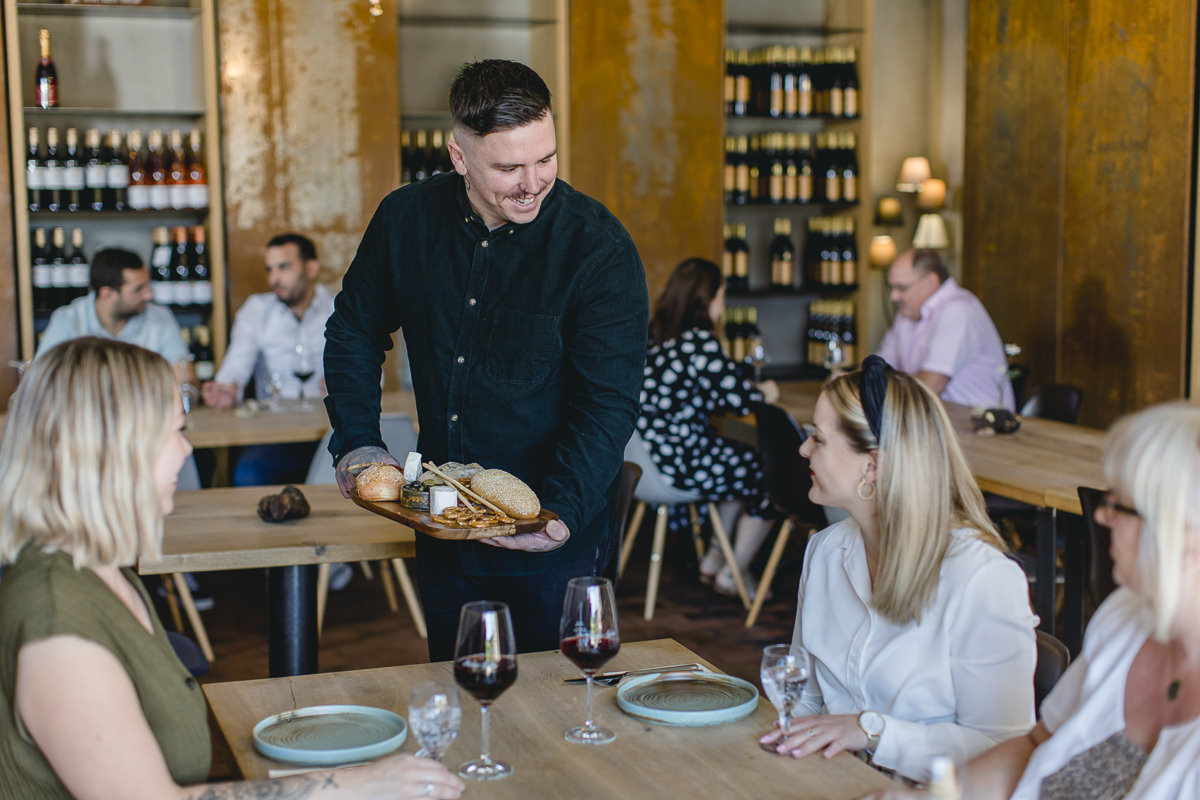 ein Vinothek Mitarbeiter serviert den Gästen eine Käseplatte mit Brot | Foto: Hanna Witte