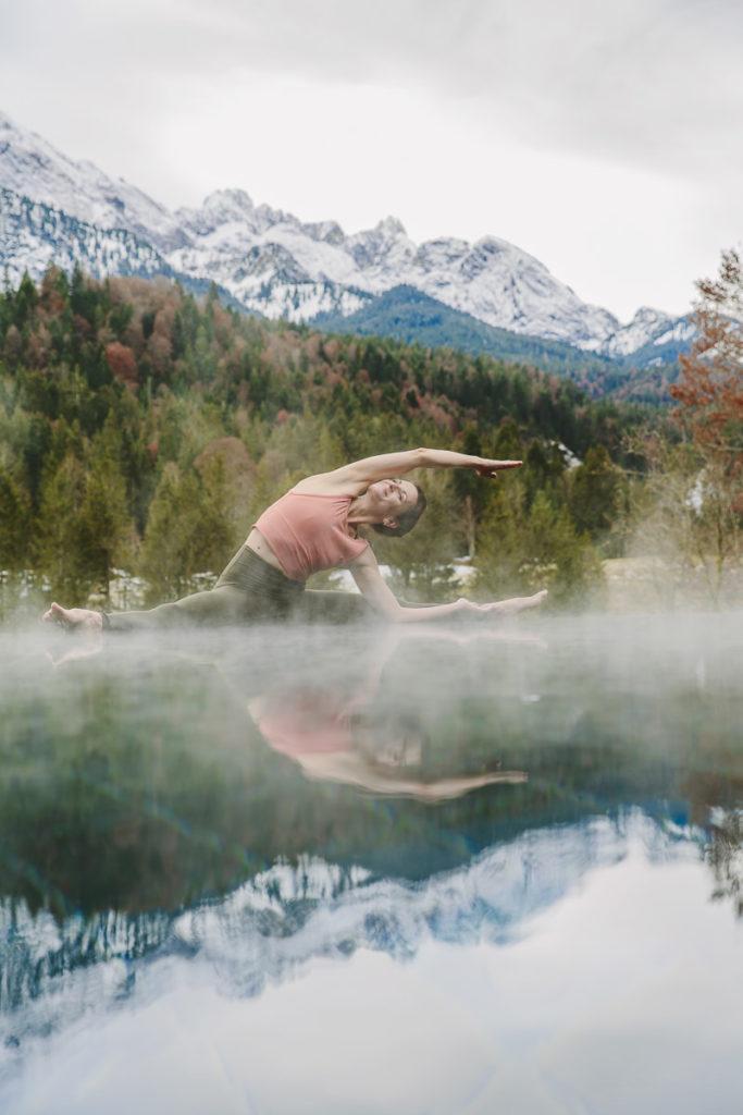Yogalehrerin Nicole Bongartz zeigt ein Asana am Infinity Pool des Yoga Retreats Schloss Elmau mit den Bayerischen Alpen im Hintergrund | Foto Hanna Witte