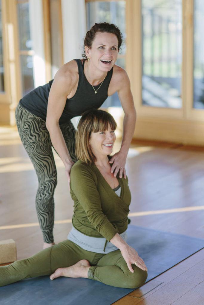 Yogalehrerin Nicole Bongartz hilft einer Kurs Teilnehmerin des Yoga Retreats von Schloss Elmau bei einer Yoga Übung | Foto Hanna Witte