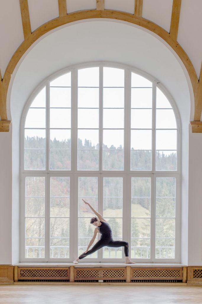 Yoga Lehrerin Nicole Bongartz macht ein Yoga Asana vor einem beeindruckend großen Fenster des Yoga Retreats Schloss Elmau | Foto: Hanna Witte