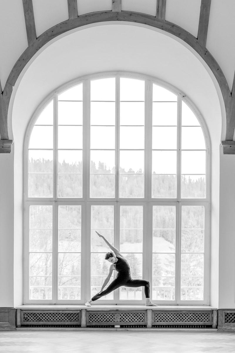 Nicole Bongartz bei einem Yoga Asana vor einem großen Fenster des Yoga Retreats Schloss Elmau   Foto: Hanna Witte
