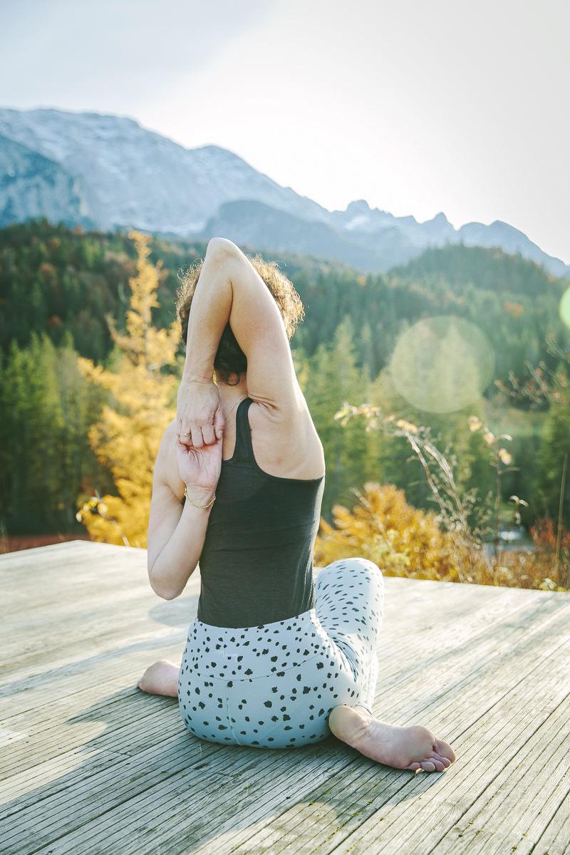 Nicole Bongartz macht draußen ein Yoga Asana vor der wunderschönen Naturkulisse der Bayerischen Alpen   Foto: Hanna Witte
