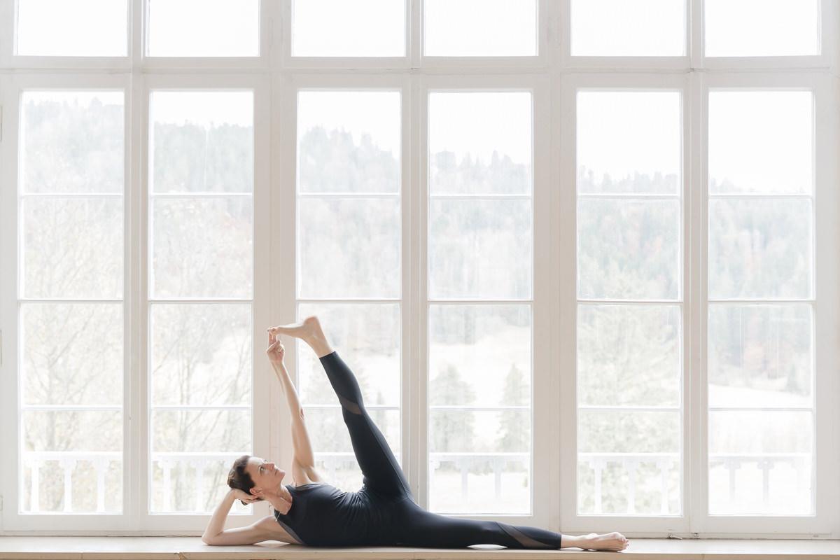 Yoga Coach Nicole Bongartz macht eine Yoga Pose vor einem großen Fenster des Yoga Retreats Schloss Elmau   Foto: Hanna Witte