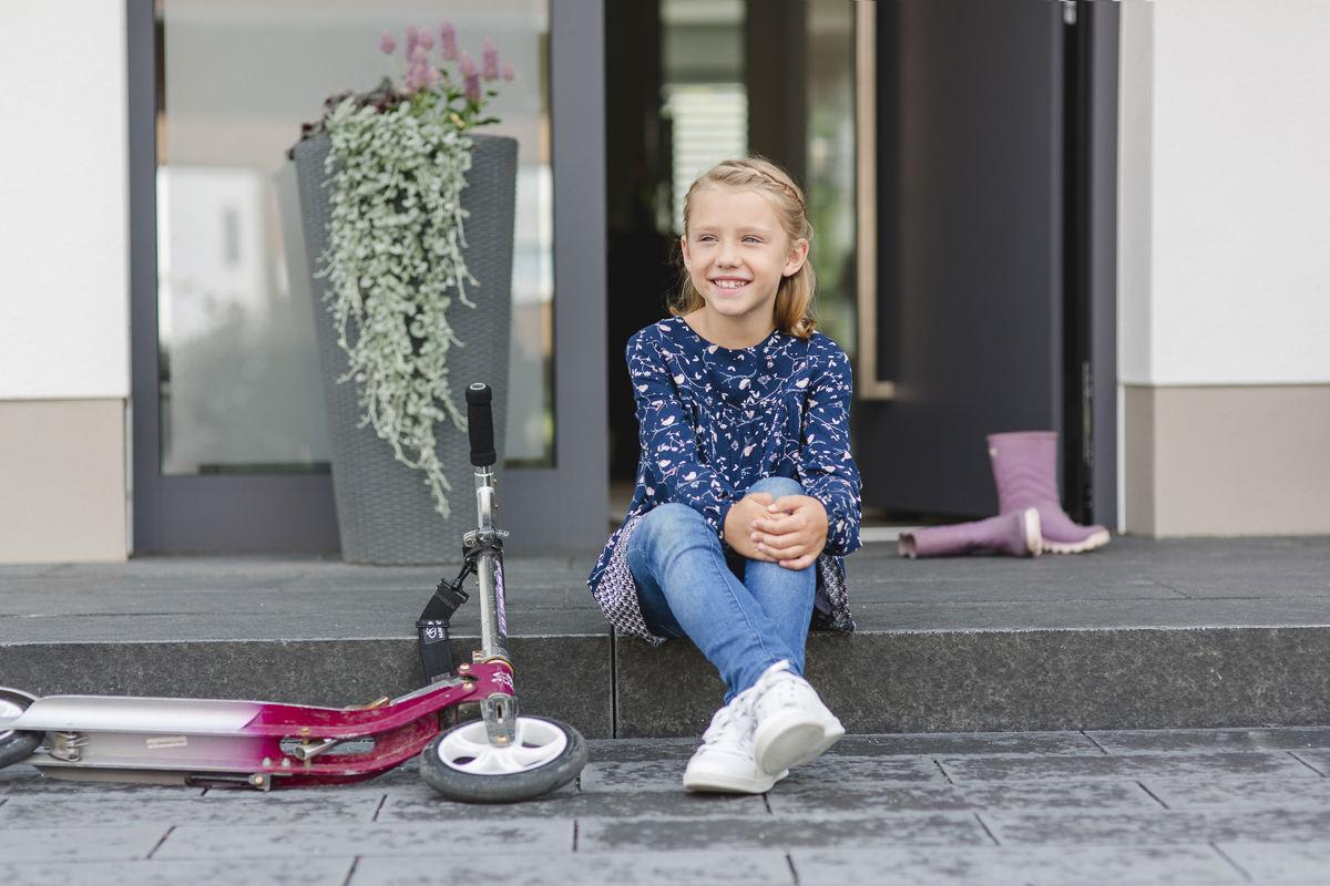 ein kind sitzt vor einer Haustüre der Firma Kleinegreber | Corporate Foto von Hanna Witte