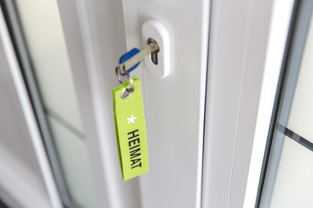 ein Schlüssel mit einem Heimat Anhänger steckt in einer Haustür | Corporate Foto von Hanna Witte