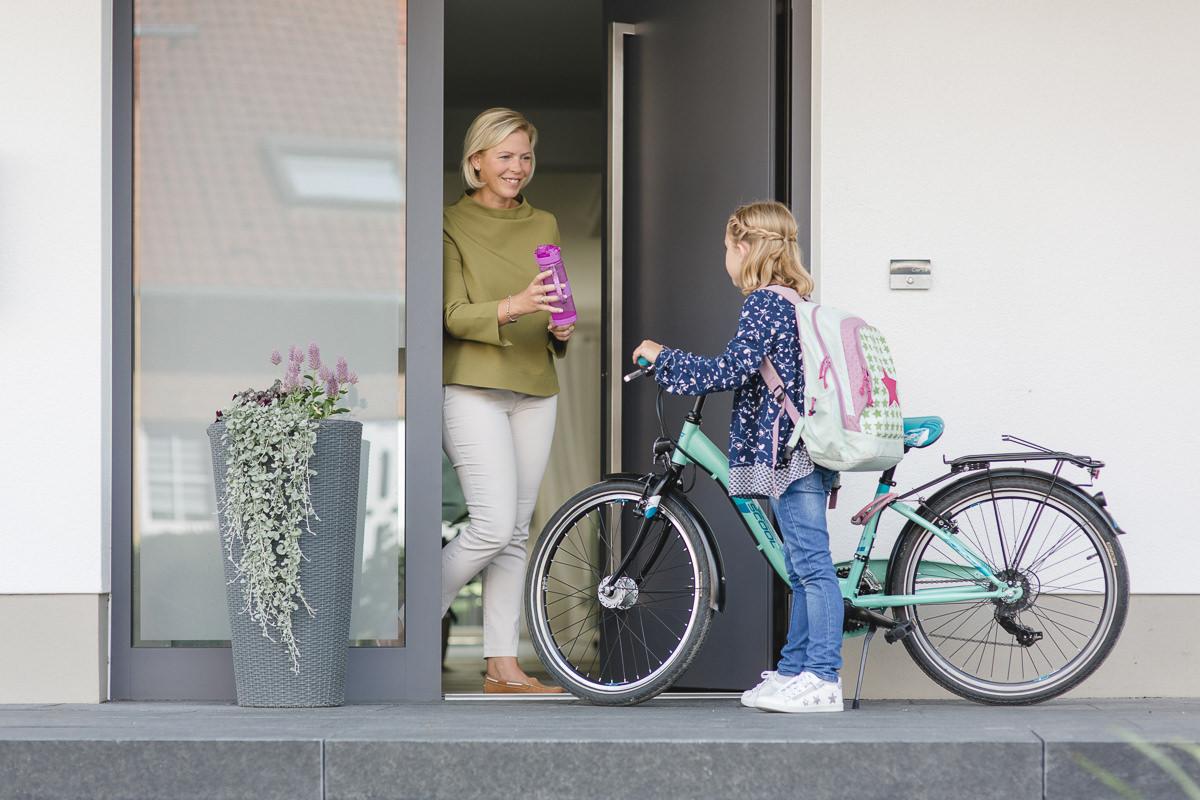 eine Mutter reicht ihrer Tochter an der Haustür eine Trinkflasche | Corporate Foto: Hanna Witte