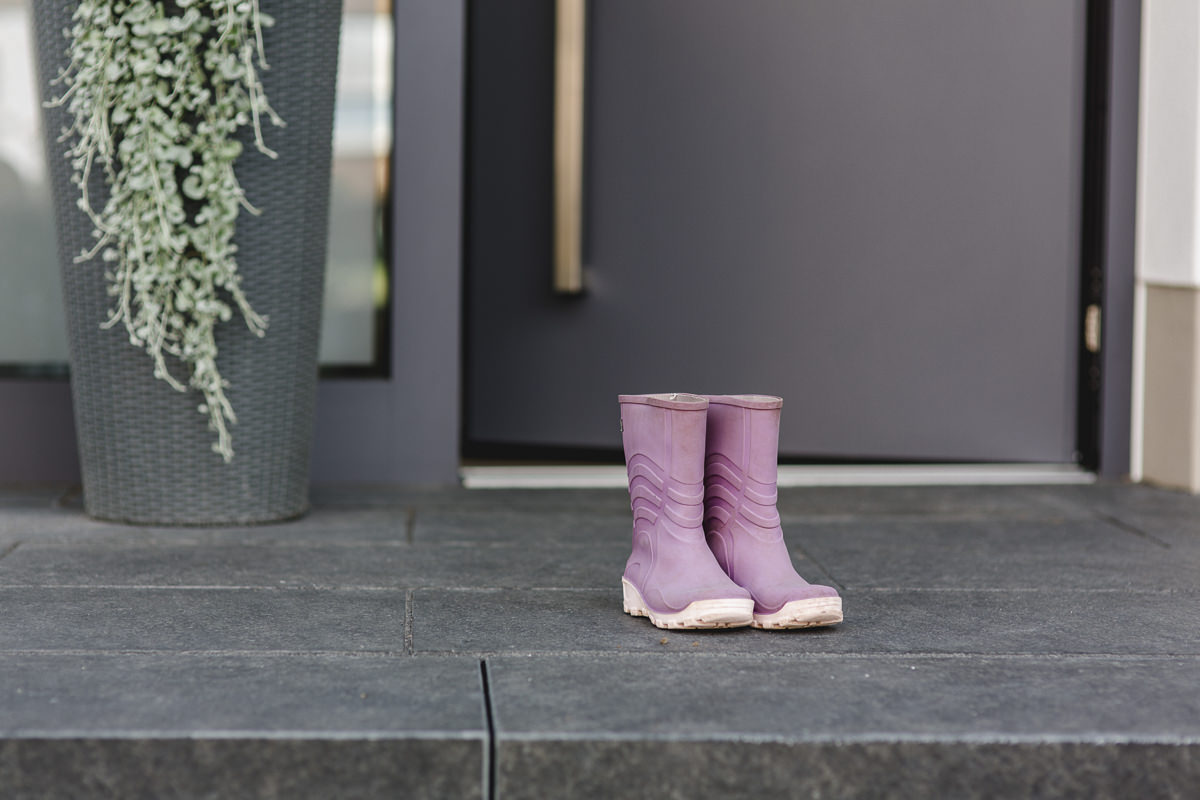 rosafarbene Gummistiefel für Kinder stehen vor einer Haustür der Firma Kleinegreber | Corporate Foto: Hanna Witte