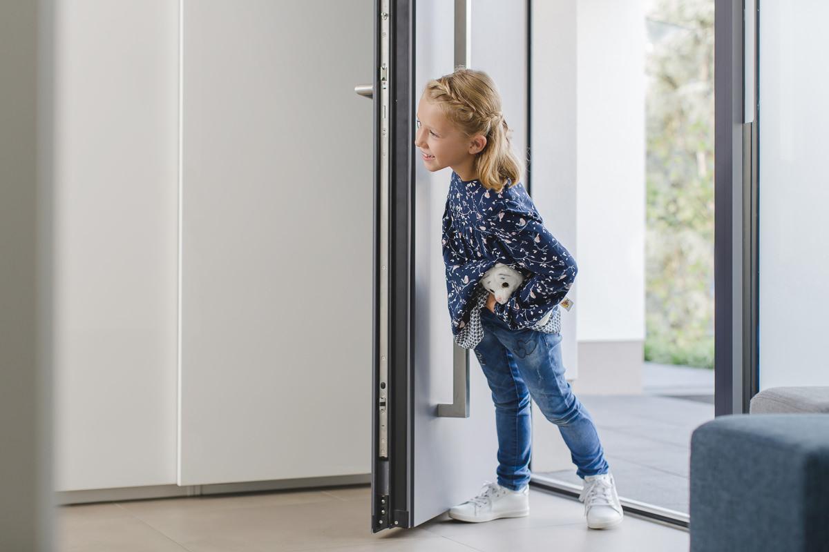 ein Mädchen schaut durch eine Haustür der Firma Kleinegreber | Corporate Foto: Hanna Witte