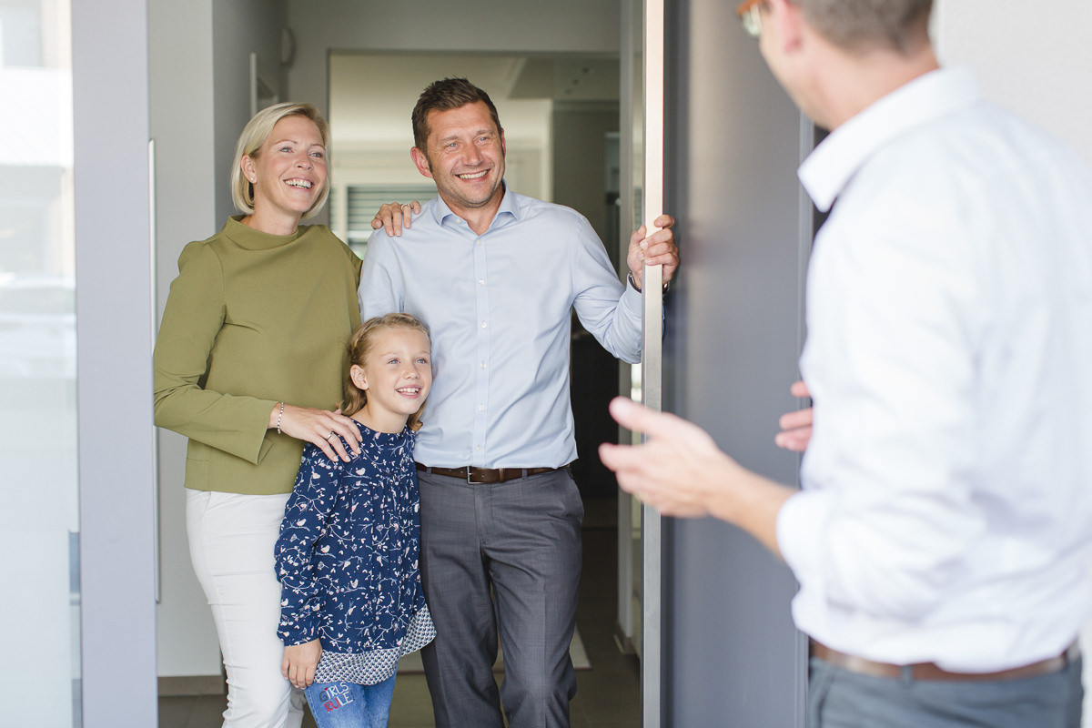 Geschäftsführer Mirko Kleinegreber redet mit einer Familie über eine Haustüre | Corporate Foto: Hanna Witte