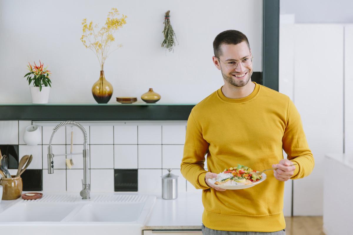 Social Media Content Fotos für EatHappy Köln: Ein junger Mann hält einen Teller mit leckerem Essen in der Hand | Foto: Hanna Witte