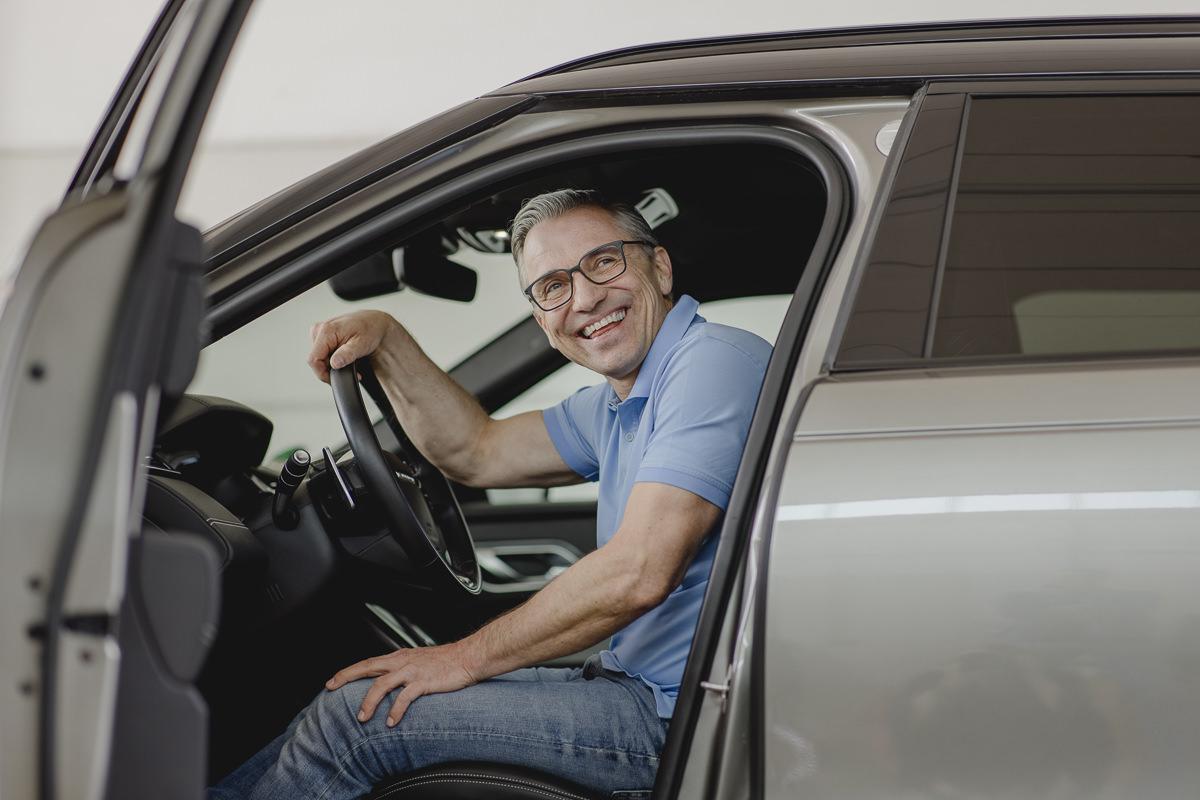 ein zufriedener Kunde der KFZ Sachverständigen Firma Rommerskirchen sitzt in seinem Auto | Foto: Hanna Witte