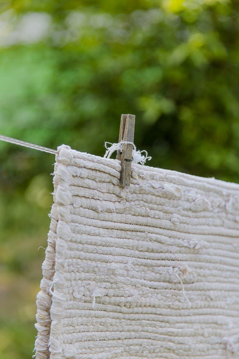 eine helle Matte hängt zum Trocknen an der Leine | Foto: Hanna Witte