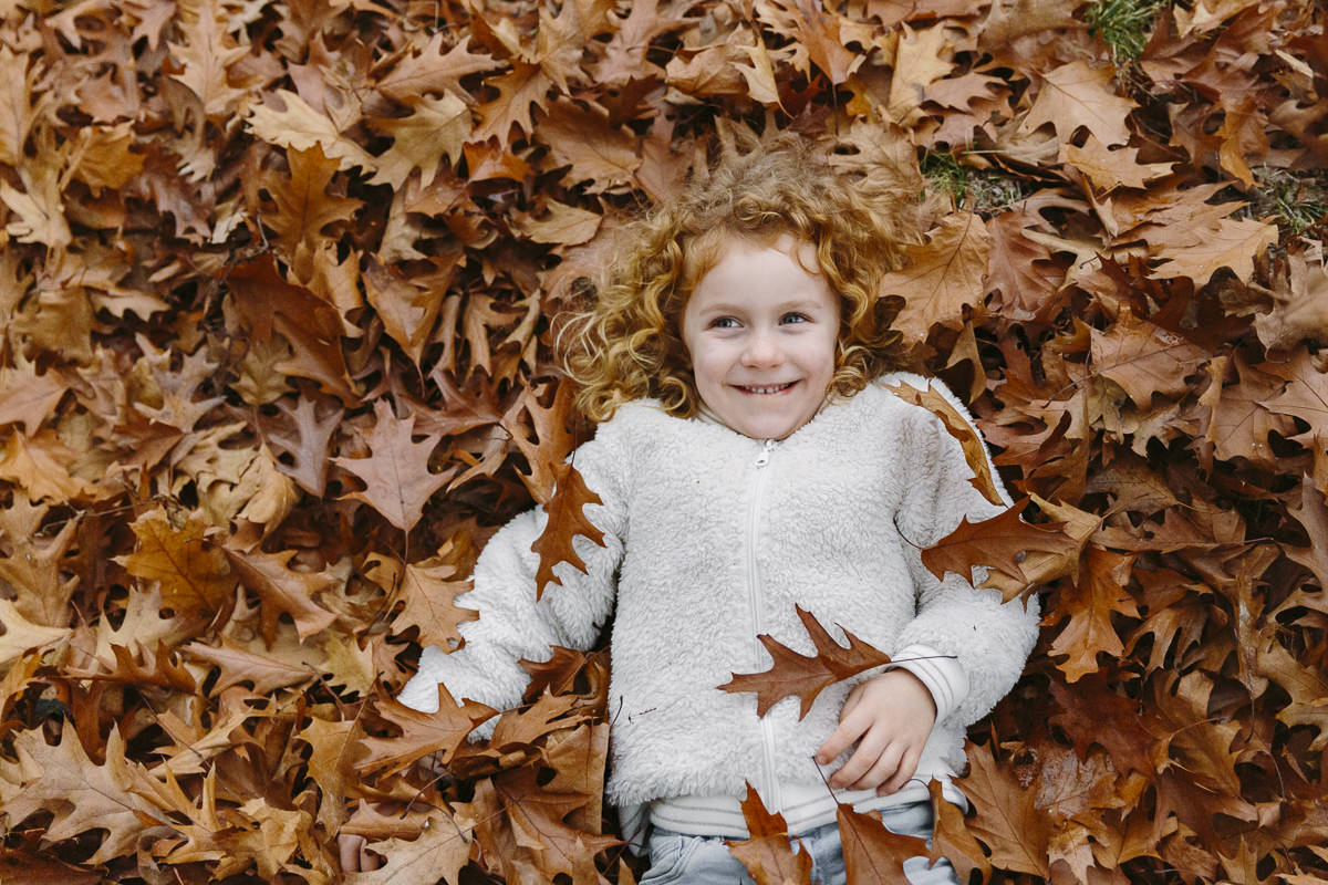 ein Kind liegt zwischen Herbstblättern   Foto: Hanna Witte