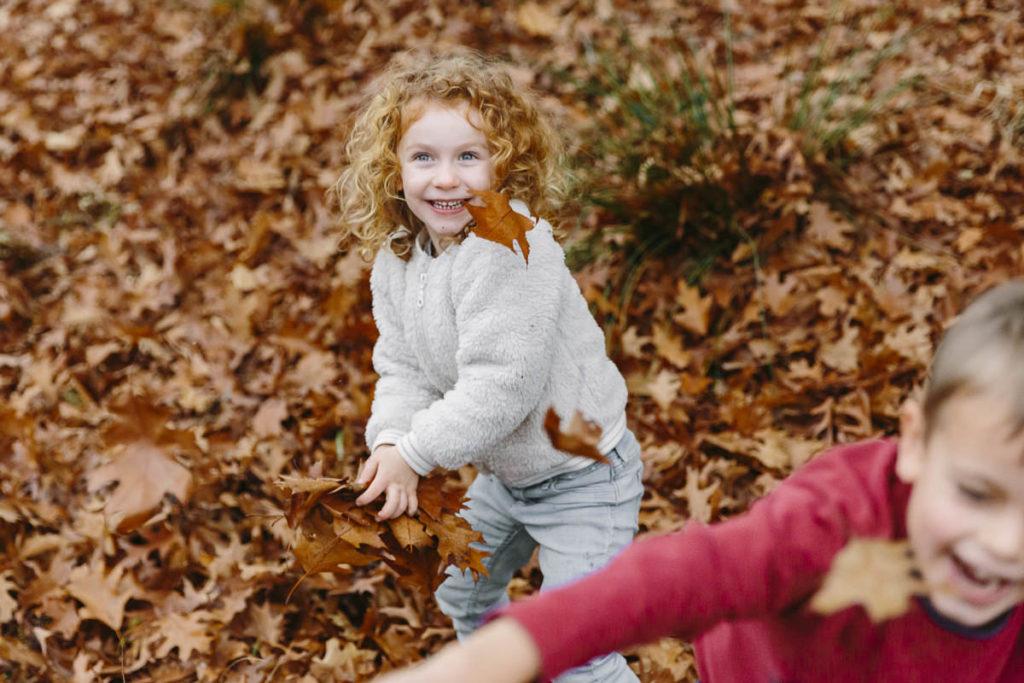 zwei Kinder spielen mit Blättern im Herbst   Foto: Hanna Witte