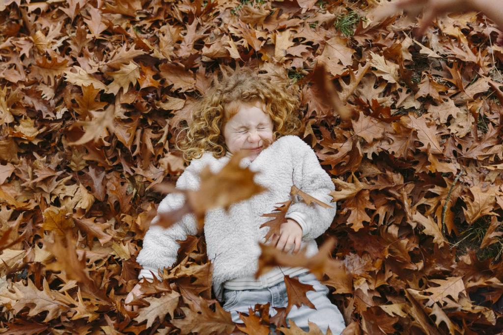 ein Kind liegt im roten Herbstlaub   Foto: Hanna Witte