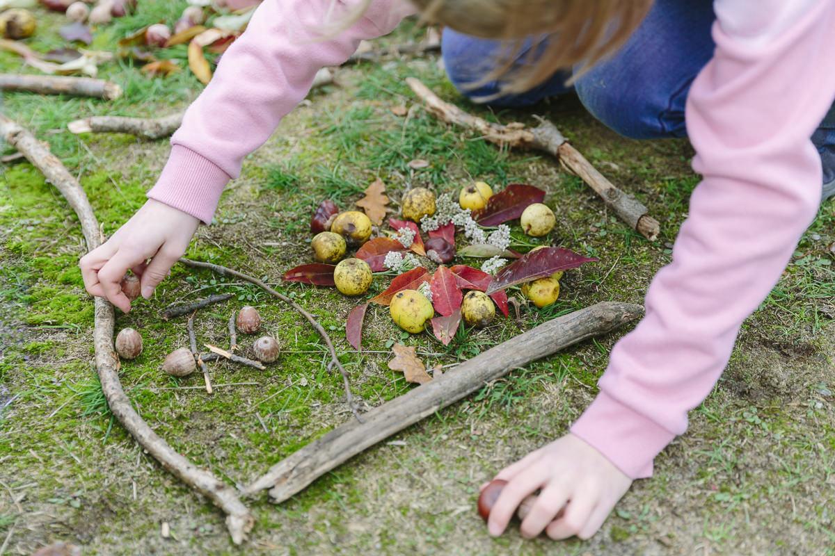 ein Kind spielt draußen mit Stöcken, Blättern, Nüssen und Zweigen   Foto: Hanna Witte