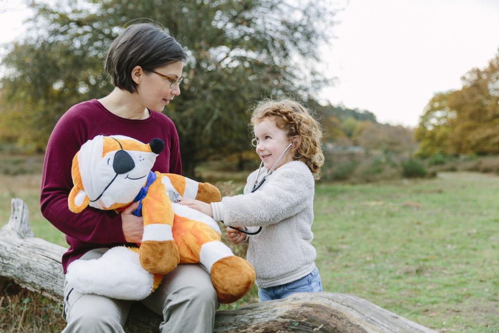 ein Kind hört ein verletztes Kuscheltier ab   Foto: Hanna Witte