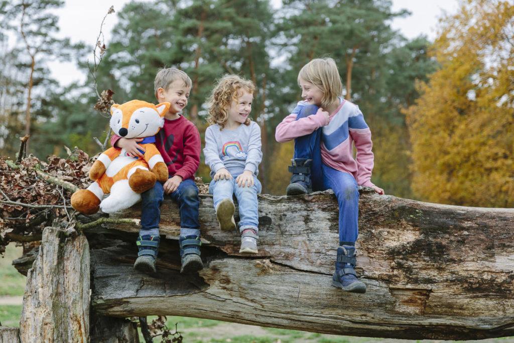 Kinder sitzen lachend auf einem alten Baumstamm   Foto: Hanna Witte